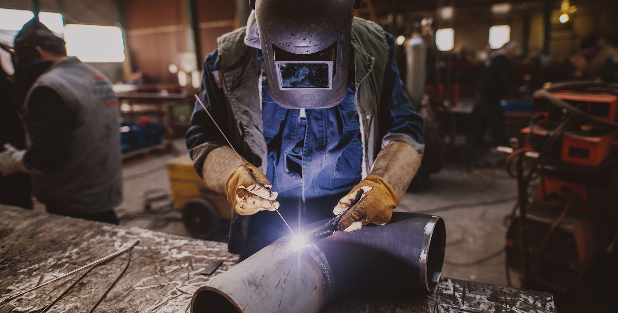 Zámečnictví Nováček s.r.o., specialisté na kovovýrobu, ocelové konstrukce, ploty, schodiště, ocelové haly, kontejnery, dopravníky. Na fotografii vidíte detail sváření ocelové konstrukce ve výrobním provozu